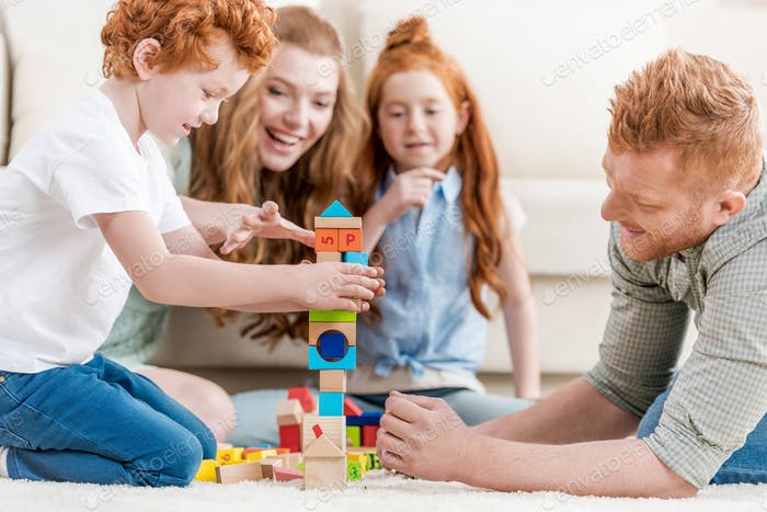 beautiful redhead family playing with constructor on floor at home, family fun at home concept