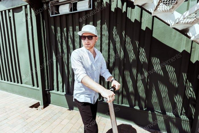Moderner Mann gekleidet weißes Hemd und schwarze Hosen stehen auf der Straße mit Elektro-Scooter