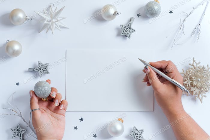 Woman's hands write letter mockup to Santa above decoration