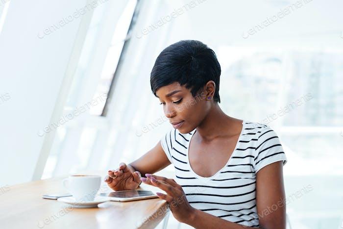 Pretty african businesswoman using tablet amd having coffee break