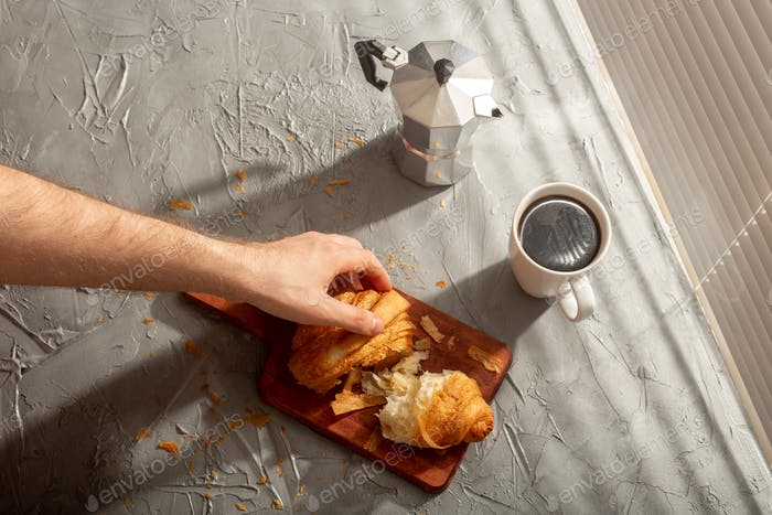 Breakfast with croissant on cutting board and black coffee. Morning meal and breakfast concept