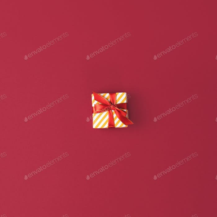 top view of festive decorated christmas gift with ribbon on red surface