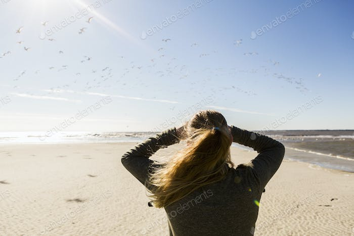 A teenage girl standing on a wide open beach, looking into the distance.