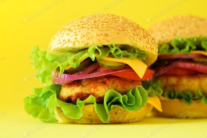 Fast Food - saftige Hamburger auf gelbem Hintergrund. Essen wegnehmen. ungesunde Ernährung Konzept mit Kopie