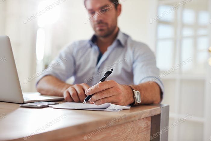 Young businessman at home office signing documents