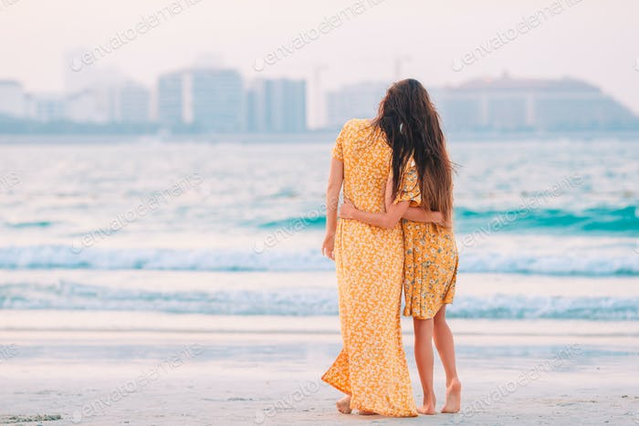 Beautiful mother and daughter at the beach enjoying summer vacation