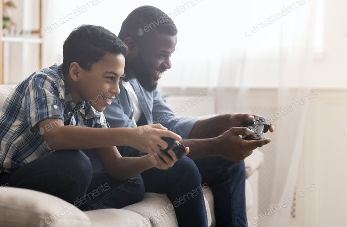 Afro father and son playing video games with joysticks