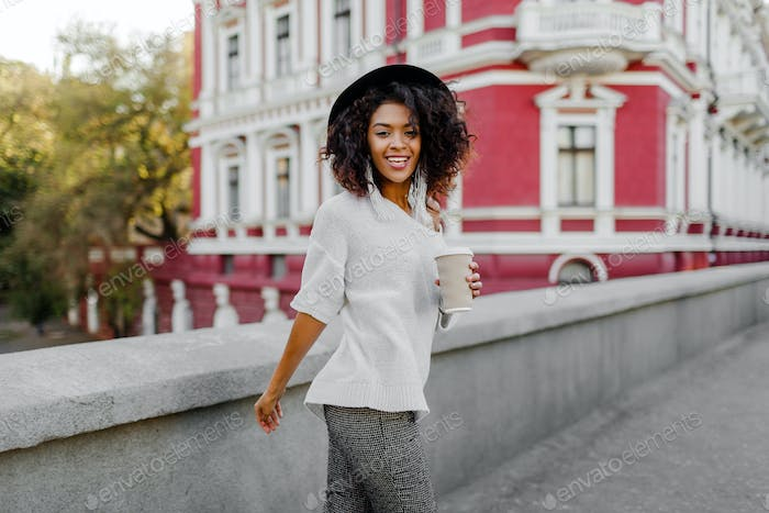 image of smiling pretty black woman in white sweater and black hat