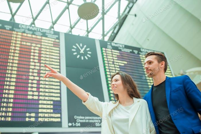 Junge Mann und Frau am internationalen Flughafen mit Blick auf die Fluginformationstafel