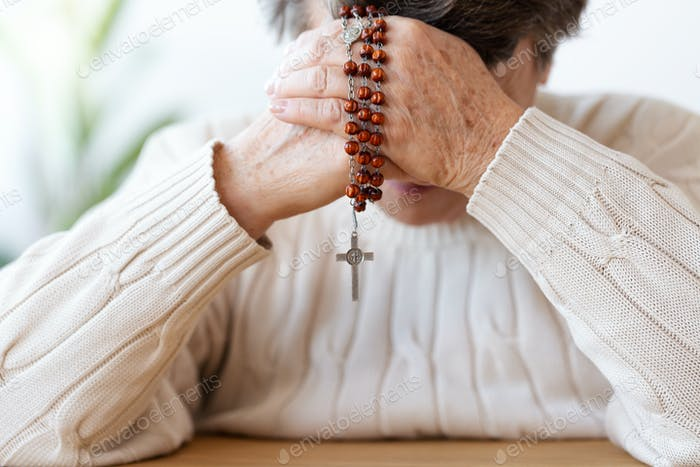 Close-up of religious senior person praying with red rosary. Foc