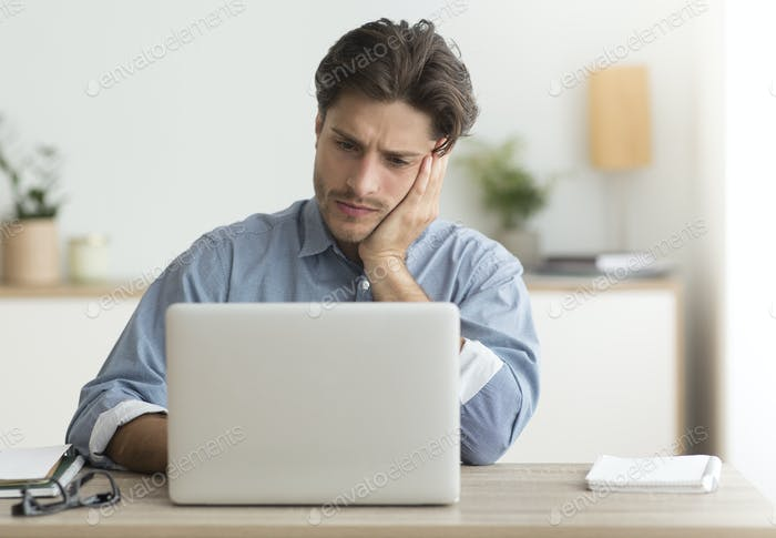 Unhappy Office Manager Sitting At Laptop Working In Office