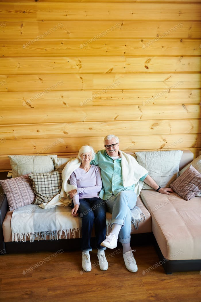 Affectionate senior couple in casualwear relaxing on sofa