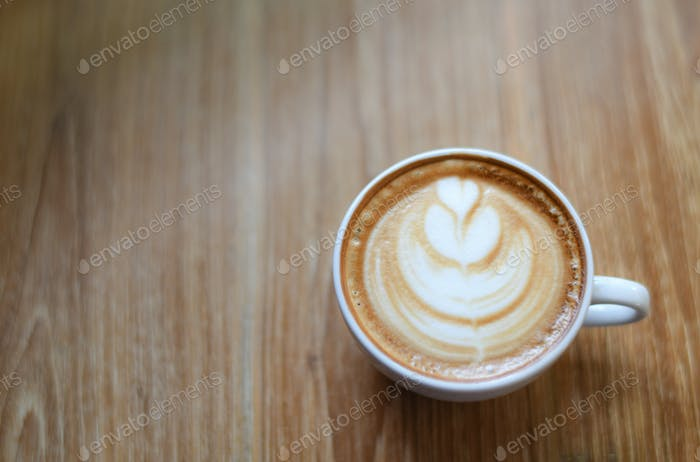 Glass of white latte coffee on beautiful wooden floors Top with leaf pattern.
