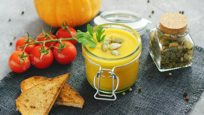 Creamy pumpkin soup in jar with bread and tomatoes