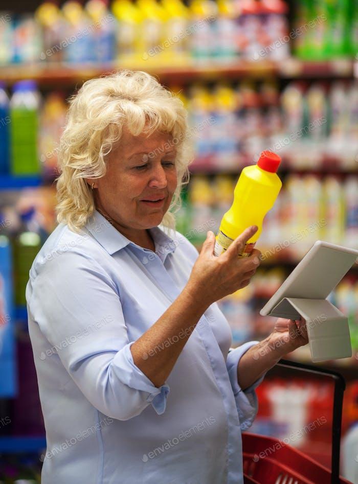 Senior Frau mit Pad Lesen des Waschmitteletiketts