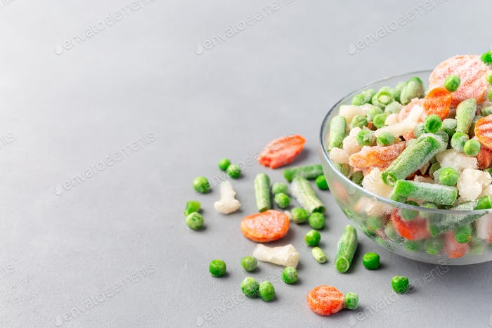 Bowl with frozen vegetables, green peas, carrot, cauliflower,  green beans, horizontal, copy space
