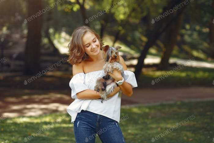 Cute girl in white blouse playing with little dog
