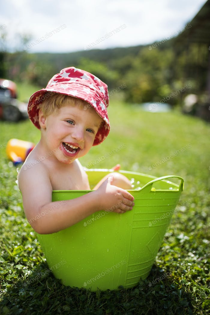 Small boy with a hat in bucket outdoors in garden in summer, playing in water.