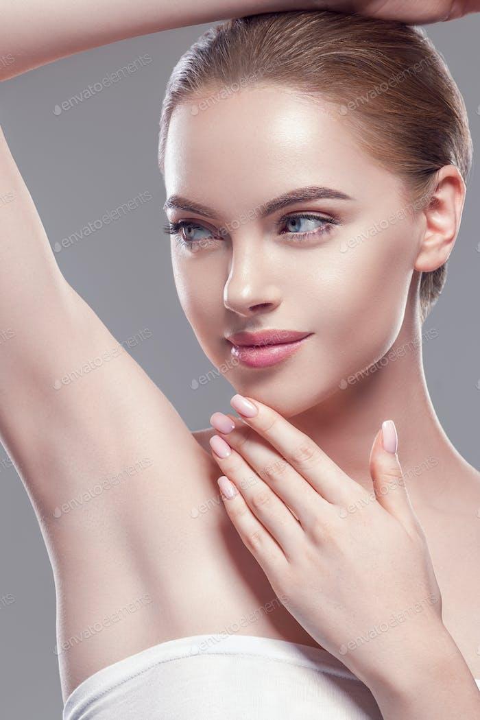 Armpit woman hand up deodorant care depilation concept. Gray background. Studio shot.