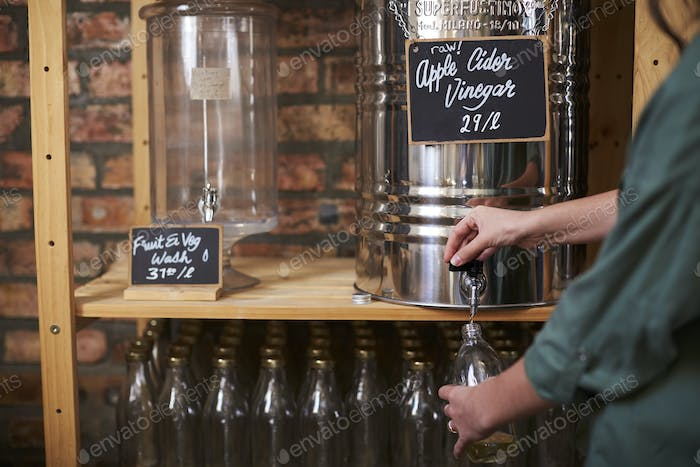 Man Filling Container With Cider Vinegar In Sustainable Plastic Free Grocery Store