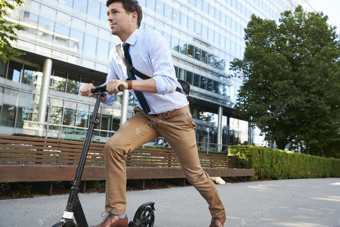 Young Businessman Commuting To Work Through City On Scooter