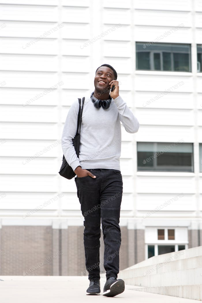 Full body happy young black man walking and talking with cellphone