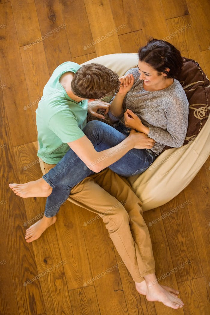 Cute couple laughing together on beanbag at home in the living room