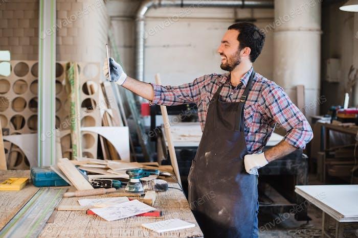 Vertical de un carpintero de pie en su Estudio de carpintería y sosteniendo tableta Digital