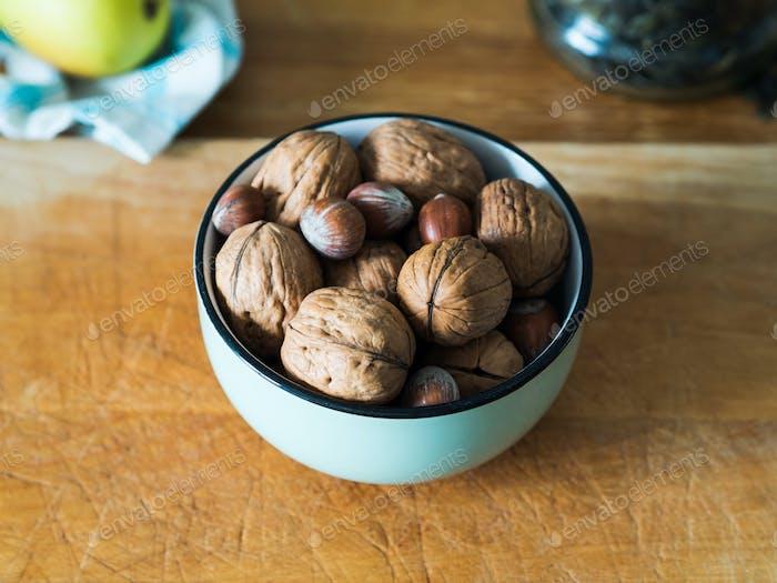 Walnuts and hazelnuts in green bowl