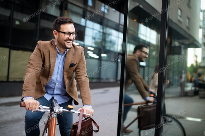 Young businessman riding on his bicycle. Going everywhere by his bike
