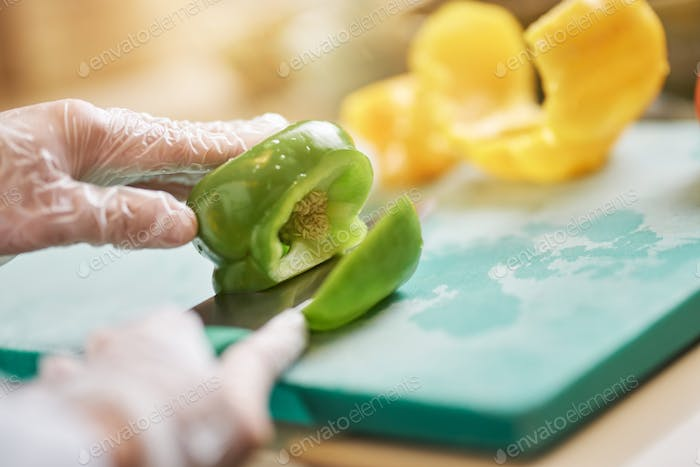 Chef in gloves cutting and preparing vegetables