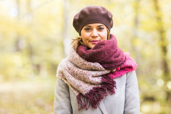 Autumn, nature, people concept - beautiful young woman in a grey coat and a beret standing in the