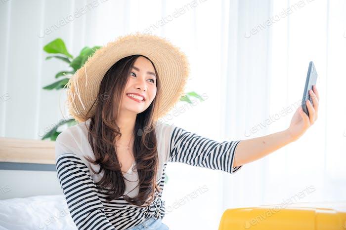 Beautiful young woman traveler taking selfie