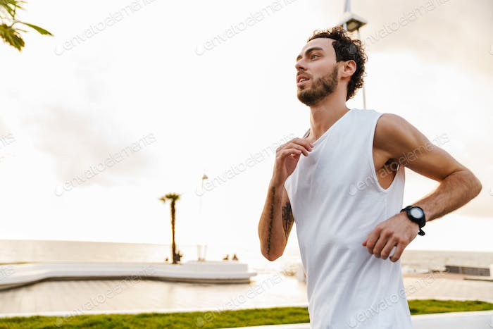 Focused unshaven guy running while working out