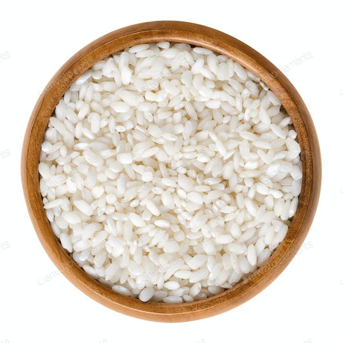Arborio risotto rice in wooden bowl over white