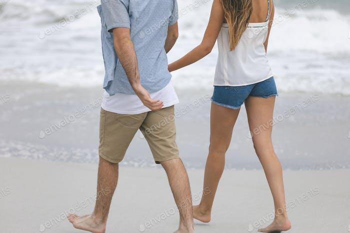 Rear view of caucasian couple walking  on beach