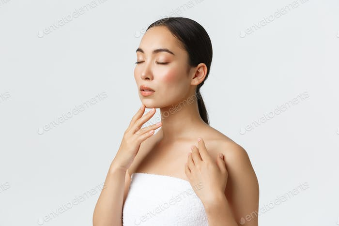 Feminine and tender young asian woman in towel close eyes, gently touching clean perfect skin