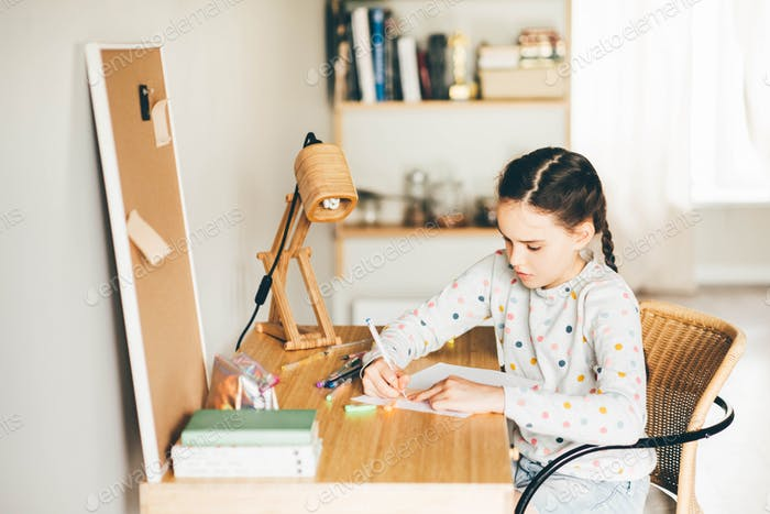 Caucasian girl sitting at the desk and writing in a notebook and doing homework.