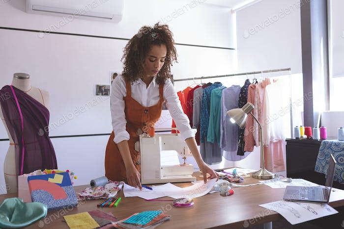 Vorderansicht der jungen Mixed-Race-weiblichen Modedesignerin, die im Designstudio arbeitet