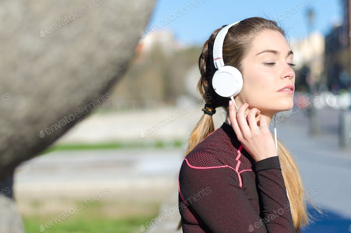 healthy woman resting and listening music with mobile phone while doing yoga and workout