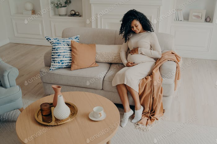 Beautiful afro american lady sitting on cozy sofa and expecting baby, looking down on her belly