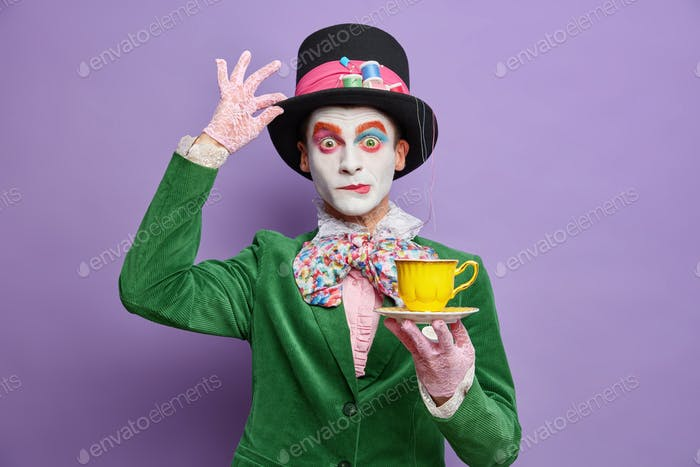 Time for having tea. Aristocratic gentleman with bright makeup has image of fictional character hold