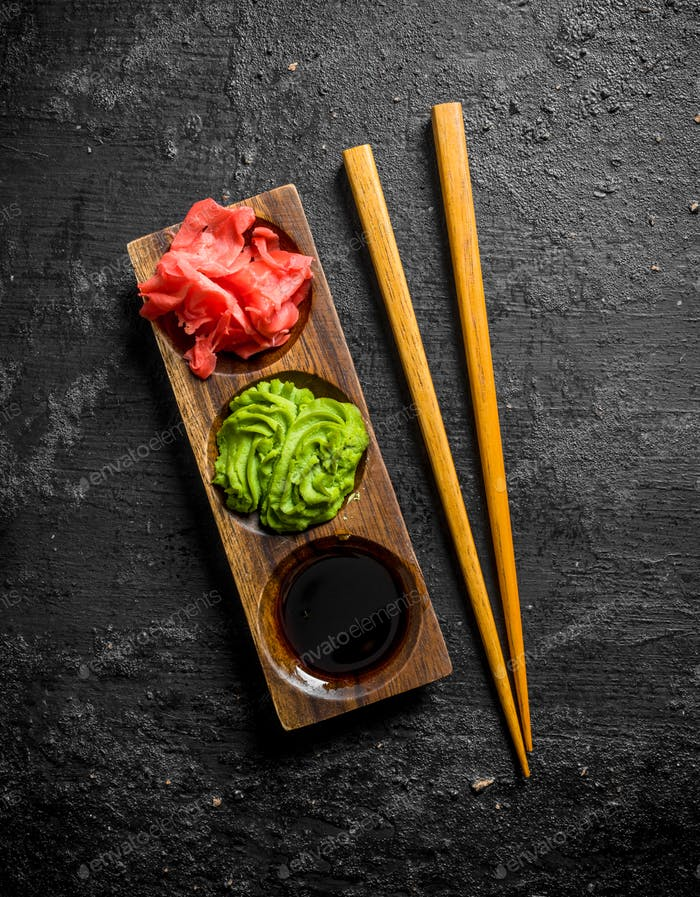 Wasabi, marinated ginger and soy sauce in a wooden stand with chopsticks.