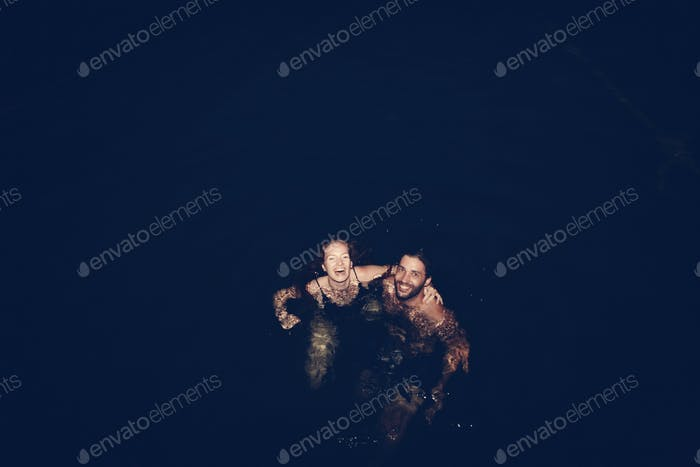 Couple playing in the dark water