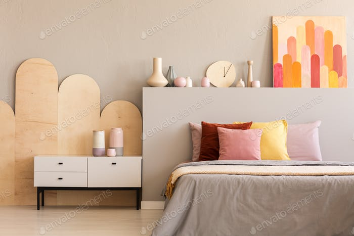 Colorful painting on grey bedhead of bed with cushions in bedroo