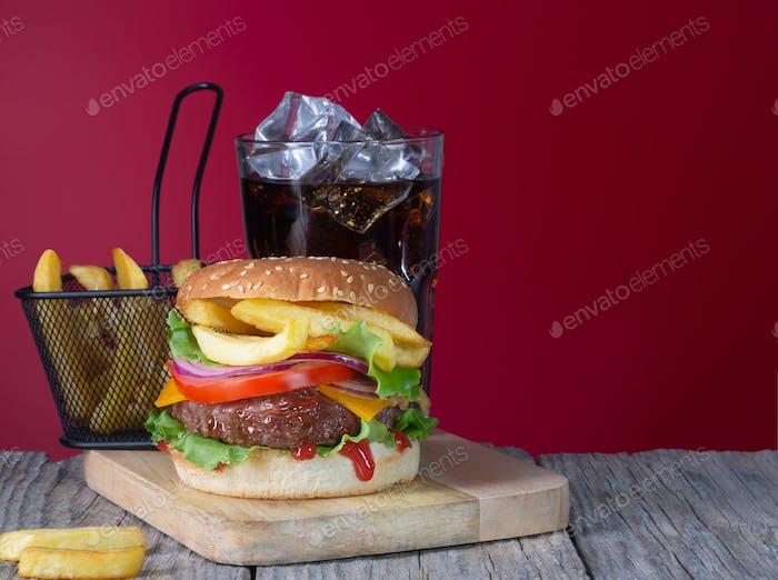 Frischer saftiger Rindfleischhamburger mit Pommes frites und Cola auf Holzhintergrund platziert