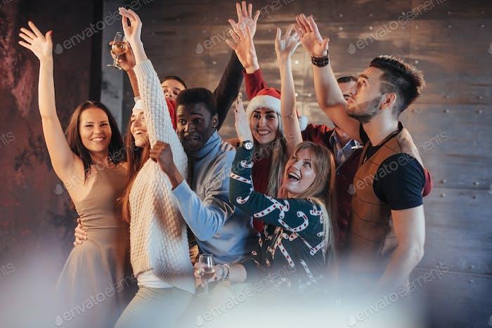 Gruppe fröhlicher junger Menschen mit Wunderkerzen und Champagnerflöten