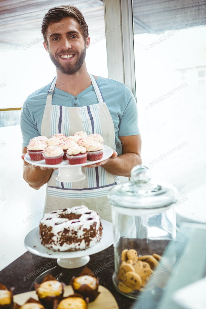 Smiling worker holding cupcakes behind the counter at bakery