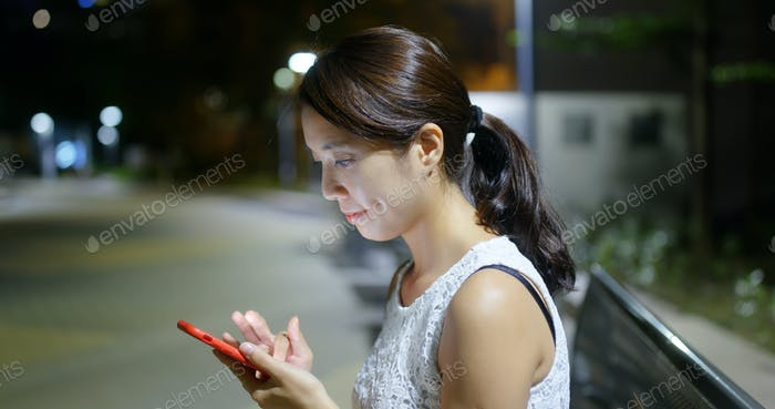 Woman use of cellphone in the city in the evening
