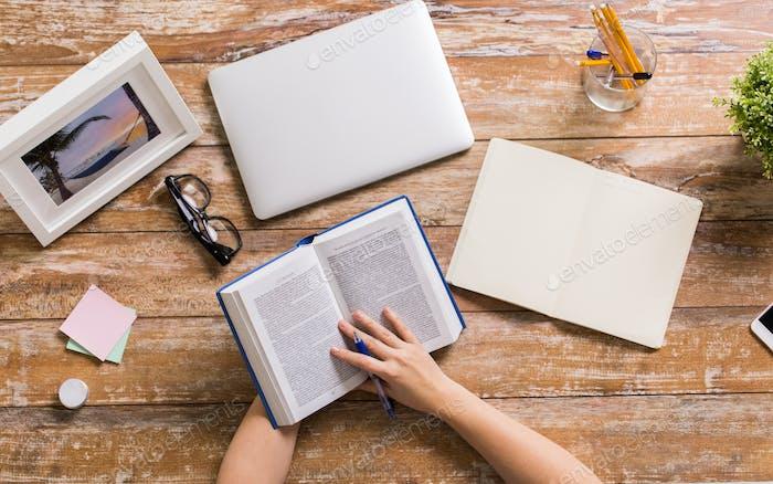 Hände der Frau lesen Buch am Holztisch